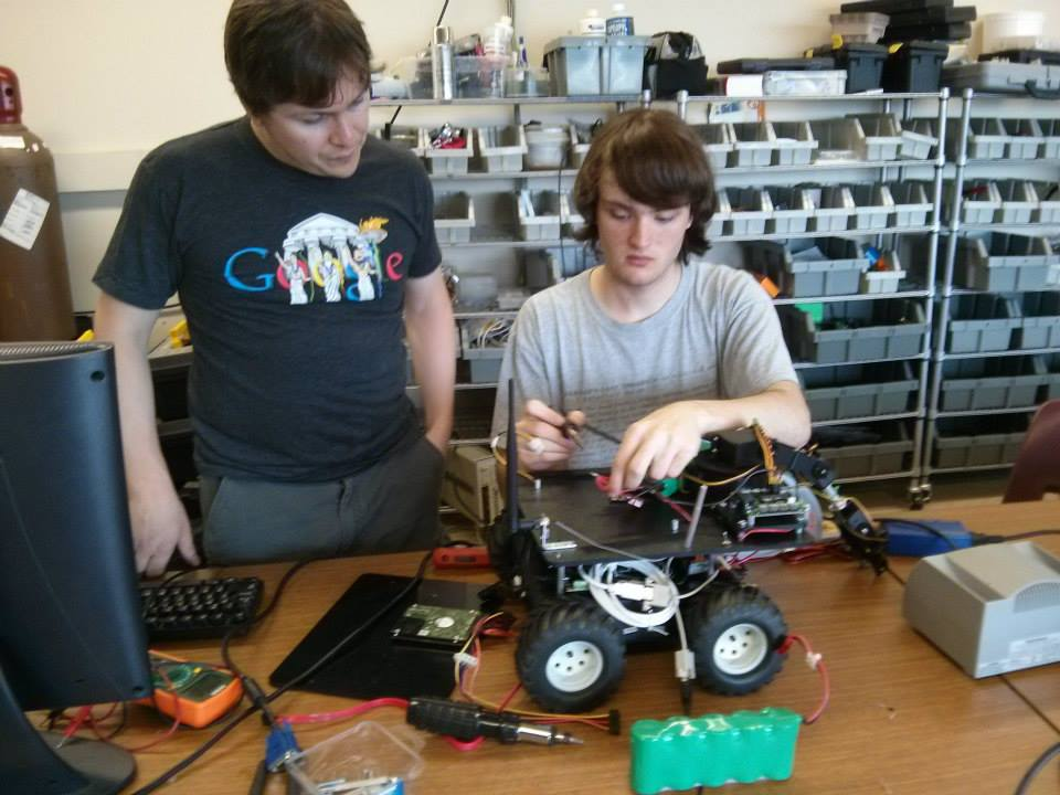 The Agency co-founder, Jesse Rosalia (left), works with Nick Johnson on the robot in 2014.